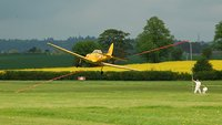 The chipmunk pilot attempts to pick up a ribbon on his starboard wing